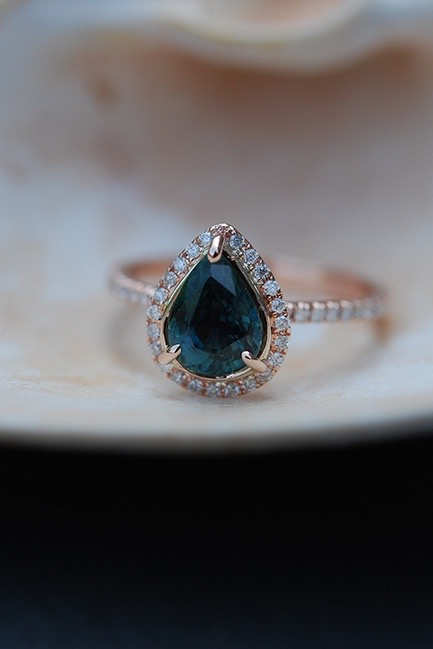 A pear-shaped sapphire engagement ring with diamond halo and rose gold band sits on a table.