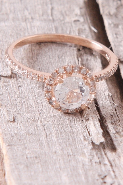 A vintage-style round engagement ring with halo diamonds and a halo rose-gold band sits on a wooden table.