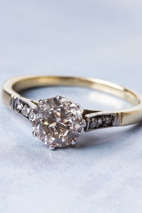 A vintage gold ring with a solitaire diamond and dark shoulders.