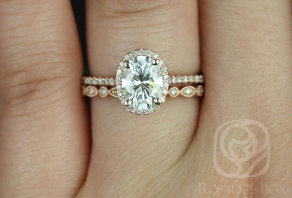 An oval diamond engagement ring with halo diamonds and rose gold band sits on a finger