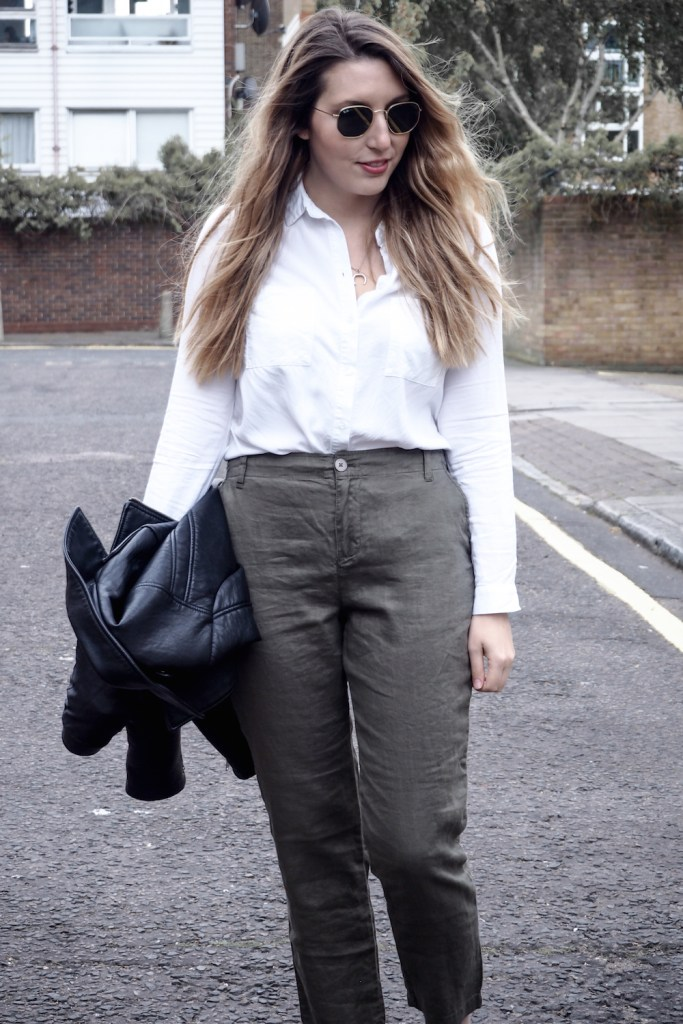 A woman walking down a London street wearing linen trousers, a white top and holding a leather jacket   Wolf & Stag