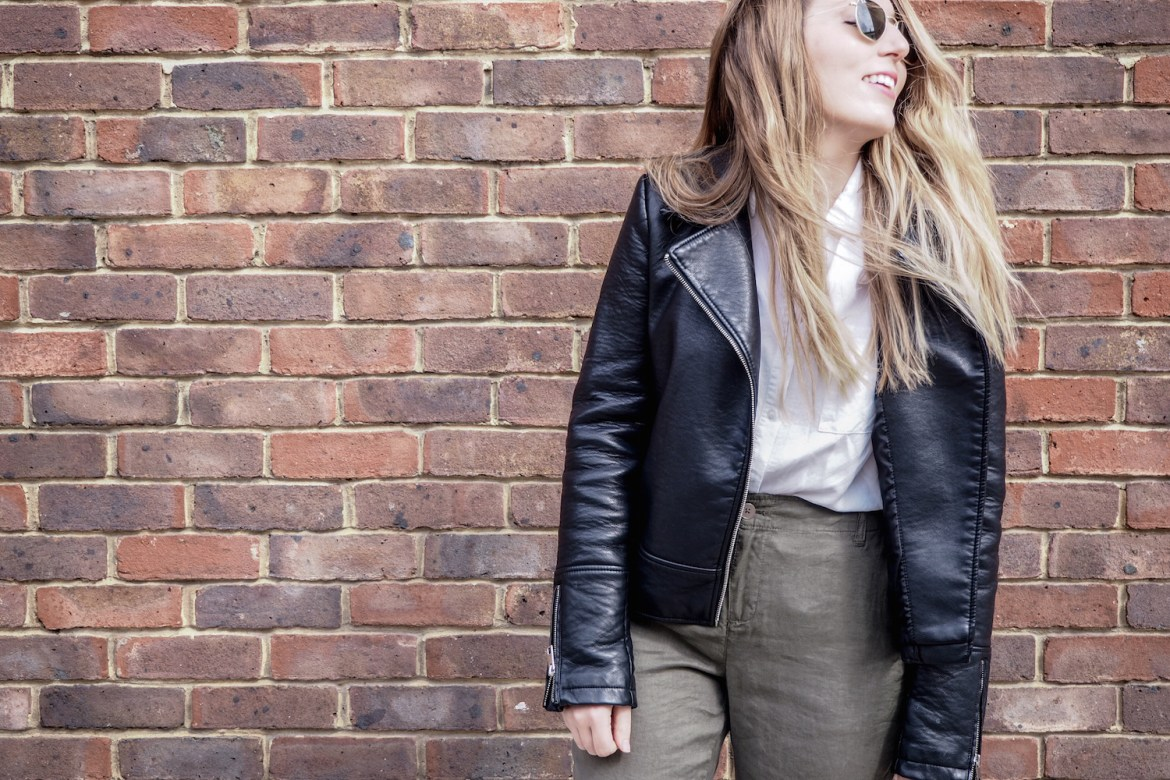 A woman standing in front of a brick wall, laughing, while wearing green linen trousers, black espadrille shoes, Ray Ban sunglasses, a white shirt and a black leather jacket   Wolf & Stag
