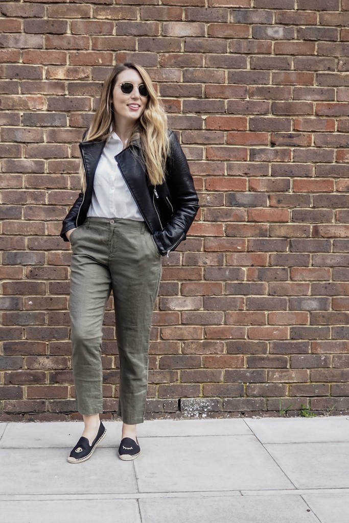 A woman standing in front of a brick wall wearing green linen trousers, black espadrille shoes, Ray Ban sunglasses, a white shirt and a black leather jacket   Wolf & Stag