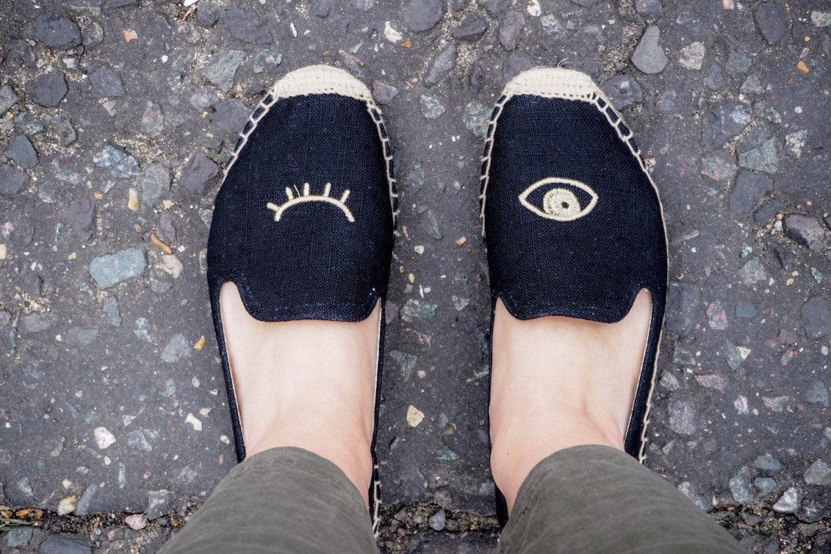 Two feet wearing winking eye black Soludos smoking slippers and the edge of linen trousers   Wolf & Stag