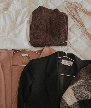 A brown cardigan, black blazer, plaid jacket, brown sweater, and white shirt lay strewn on a white coverlet bed with golden hangers, as Erin Pollard prepares to pack for her 3 week trip to Australia and New Zealand