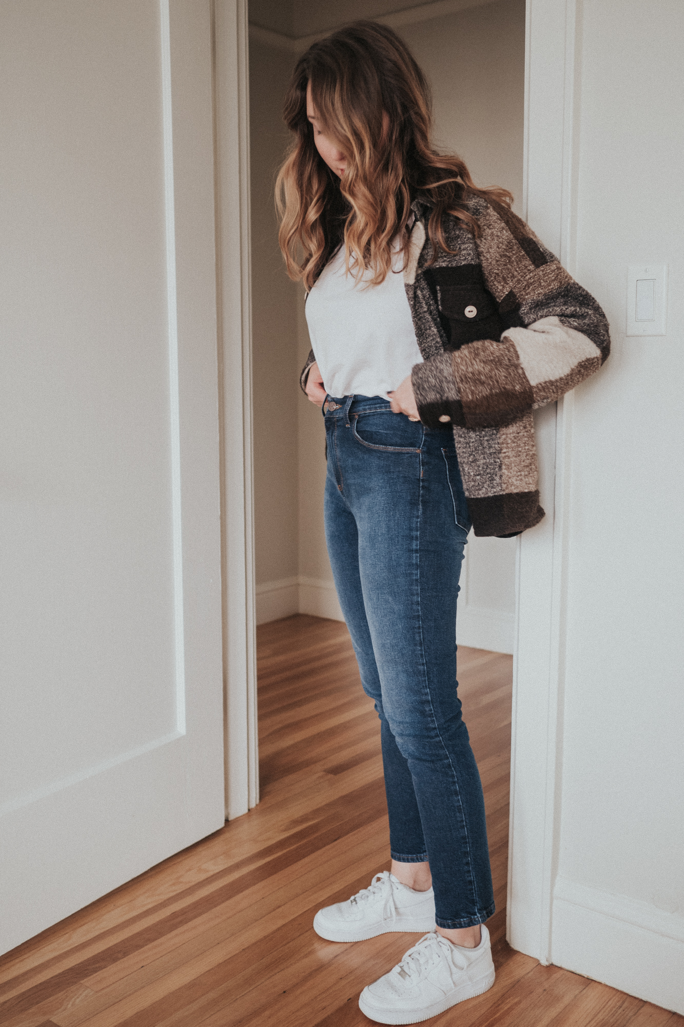 Erin Pollard stands in a doorway wearing Mott & Bow cropped white tee and mom jeans | Wolf & Stag