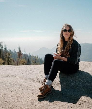 Erin Pollard high in the Sequoia mountains, wearing an Anine Bing sweatshirt, black leggings, and hiking boots