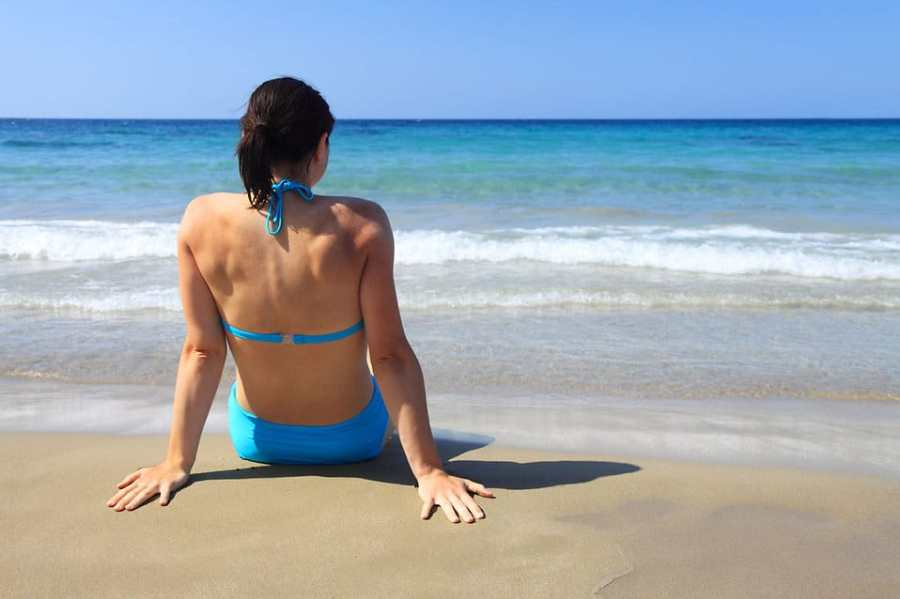beautiful-woman-sitting-on-the-beach-looking-at-the-ocean