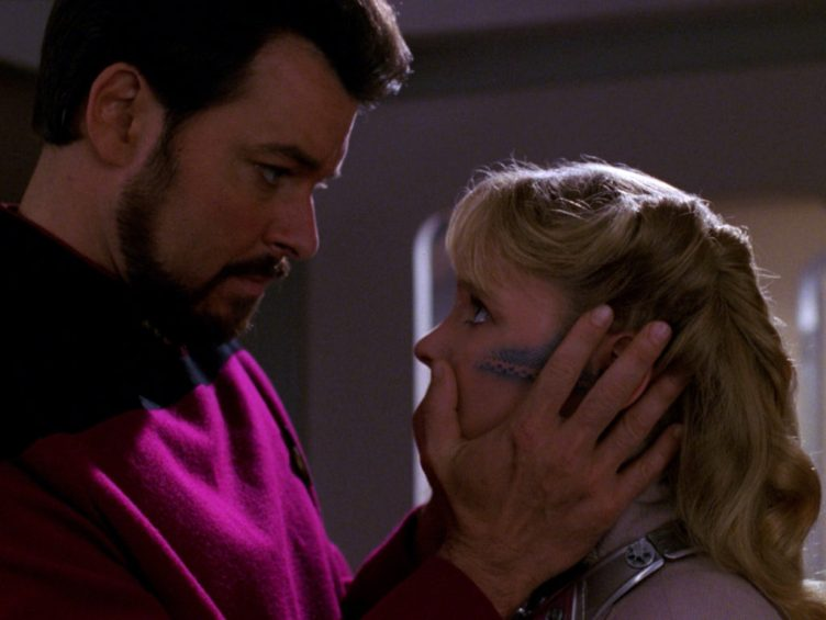 Riker holds Yuta's face as if comforting her