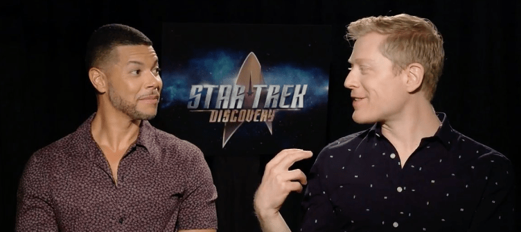 Wilson Cruz and Anthony Rapp looking fondly at each other in an interview.