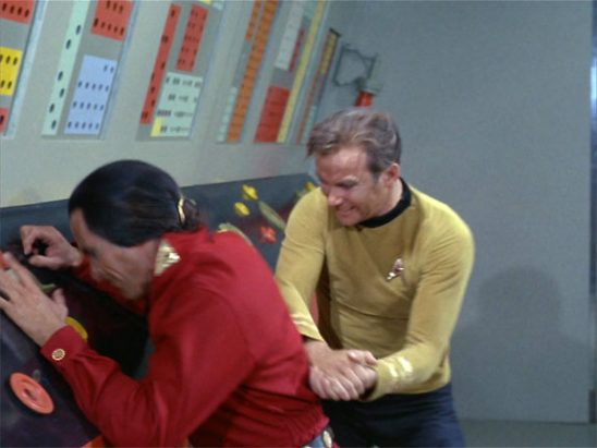 Kirk hits Khan in the back with two fists