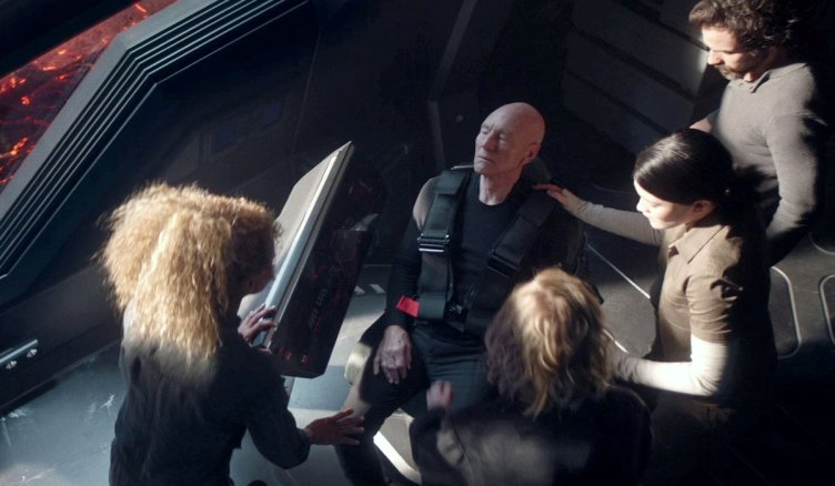 The crew rushes to Picard's side
