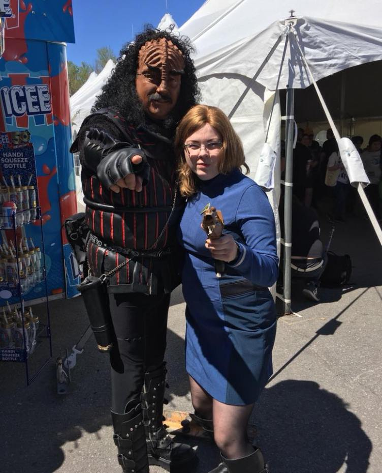 Klingon cosplayer and the author in a Starfleet cosplay, pointing at the camera