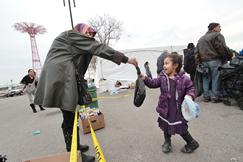 Safiyya giving necessities to a young child in Coney Island