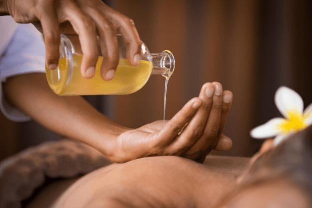 pouring diy massage oil on the hand