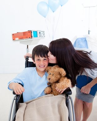 stockfresh_2316060_cheerful-little-boy-sitting-on-wheelchair-and-his-mother_sizeXS