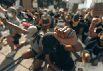 A close-up of black protesters knelt on the ground with their fists in the air.