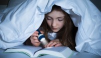 girl reading book with flashlight