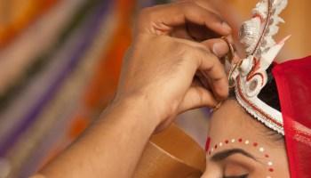 groom putting sindoor on bride's forehead