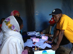 Ethiopia MFI staff discussing savings account with girl saver in Lumame