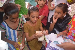 A Tejasvi account holder counts out her money before making a deposit with the visiting financial counselor
