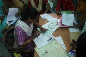 A loan officer at an Indian microfinance institution processing paperwork