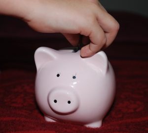 Child's hand putting money in a piggy bank