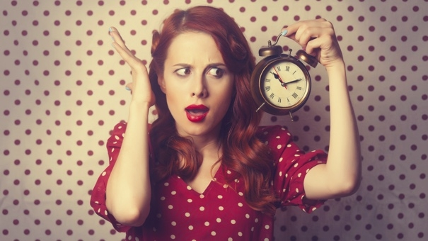 Portrait of a surprised redhead girl with alarm clock on Polka dot background.