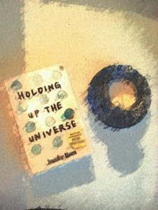 paperback book holding up the universe next to a teacup candle with a smudged painting style filter