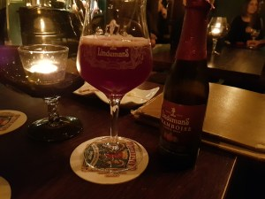 Lindermans Framboise Beer with glass on table with tealight candle in bowl