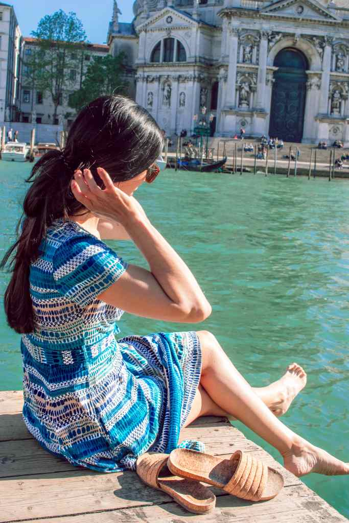 Woman sitting on dock in Venice Italy with blue dress