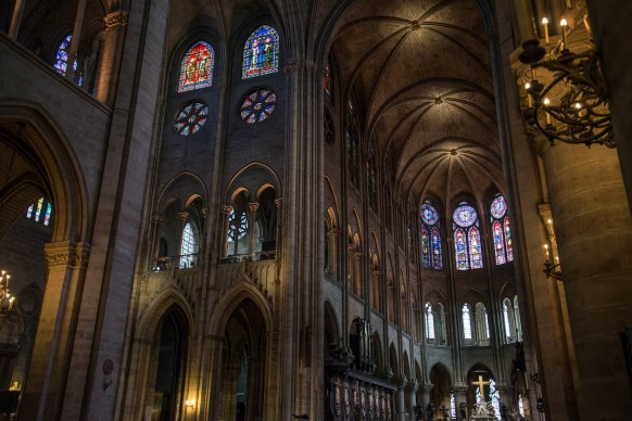 The interior of the Notre Dame cathedral is seen. Multiple arches structure the cathedral. The main crucifix is seen illuminated by stained glass.