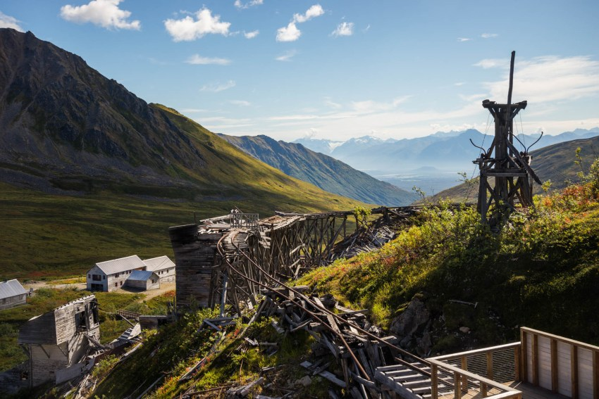 The decaying ruins of Independence gold mines rail cart track are seen in Hatchers pass Alaska. The ruins sit among the vibrant green alpine plants.