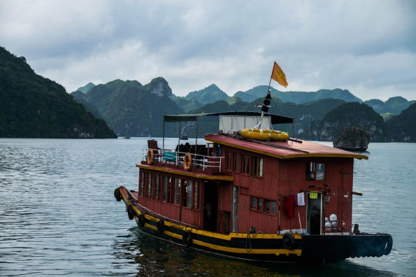 An old faded red wooden cruise boat explores Vietnam's Ha long bay. It carries a weathered Vietnamese flag among a backdrop of limestone karst mountains.