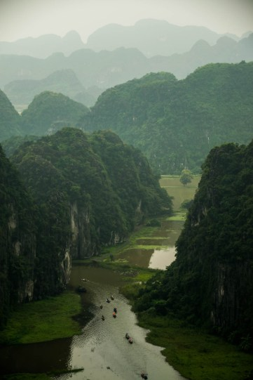 Row boats pass through an opening in Tam Coc, a flooded cave karst system near Nihn Bihn Vietnam. The jungle mountains are enveloped in a moderate fog.