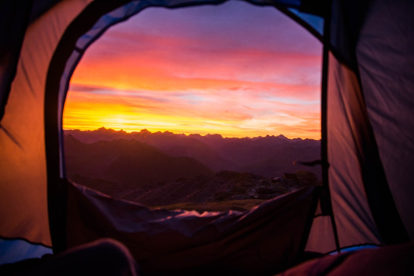 A tent door is opened to a spectacularly colored sunrise on top of a secluded mountain in hatcher's pass Alaska.