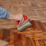 22815687 – varnishing of oak parquet floor, workers hand and brush