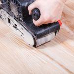 23504121 – finishing ashwood surface by hand-held belt sander