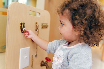 A Toddler practices working a latch