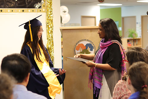 A graduate receives her diploma from the head of school