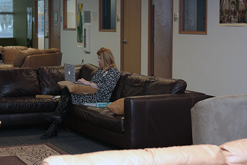 A teacher sits on a sofa and works on a laptop