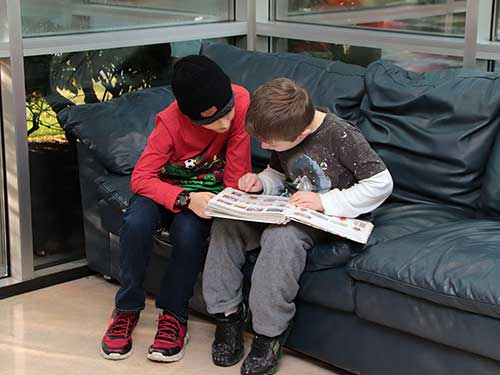 Two boys share a book, as they sit on a sofa.