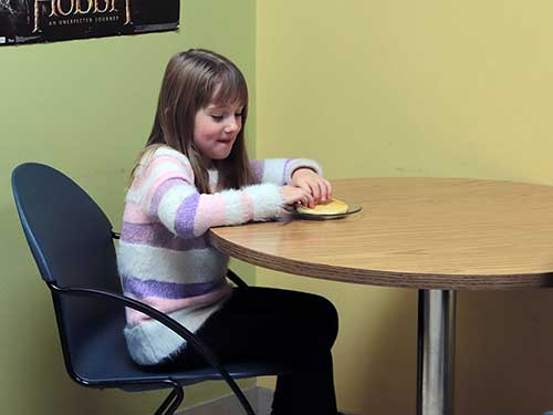 A student seated at a table breaks off a piece of pancake.