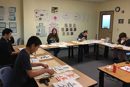 Students practicing writing Japanese characters
