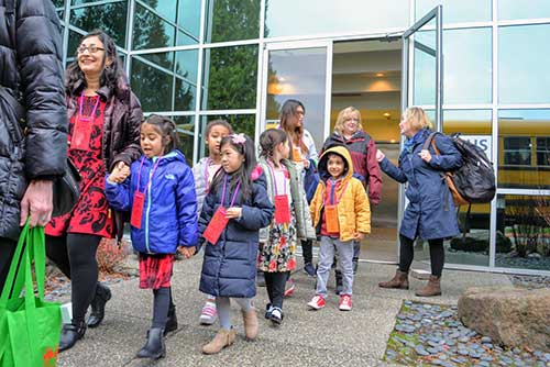 Excited kindergarteners and their grownups board the bus for The Nutcracker.