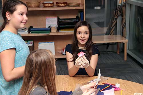 Three Upper Elementary girls make fortune tellers with paper.