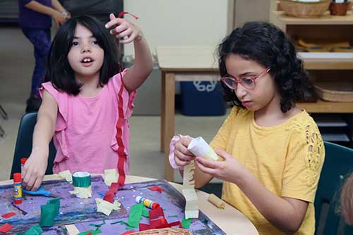 Two elementary-age girls cut and glue strips of red, white and green paper.