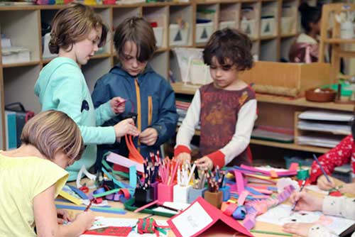 Two girls and two boys work on a paper craft.