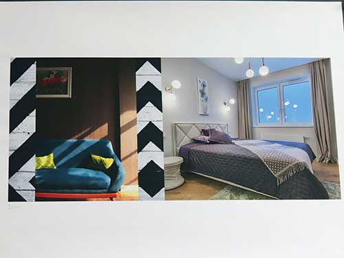 A brightly-lit bedroom; a blue chair with yellow pillows against a wood wall and a black and white chevron pattern.