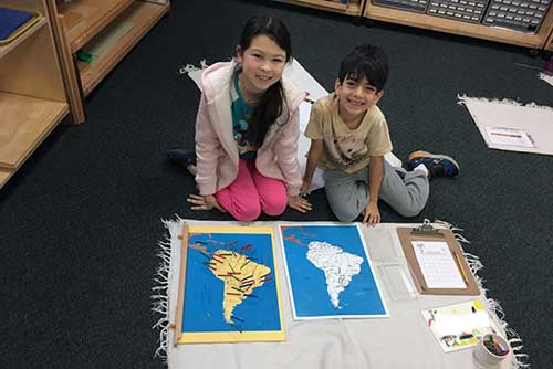 A girl and a boy smile in front of their South America map work.
